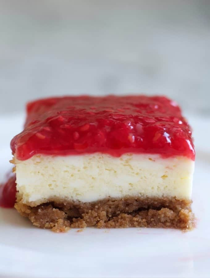 Raspberry Cheesecake square cut on a plate.