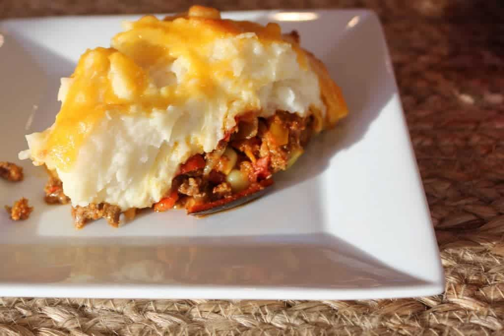 Shepherd's pie has a hamburger filling spiced with a southwestern flair, topped with creamy mashed potatoes and melted shredded cheese. A comforting, filling casserole. http://HomemadeFoodJunkie.com