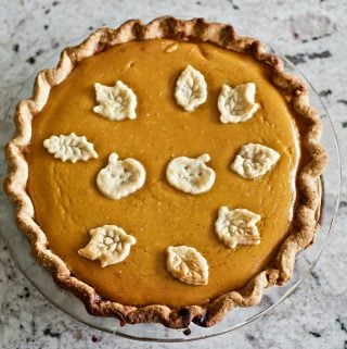 Pumpkin pie with dough cut outs on top two pumpkins and fall leaves bake in to celebrate the season