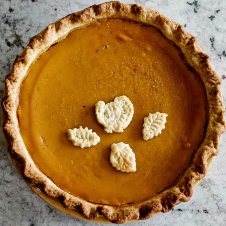 Pumpkin pie filling from fresh pumpkins baked in a sourdough pie crust with a turkey and three fall leaf dough toppers