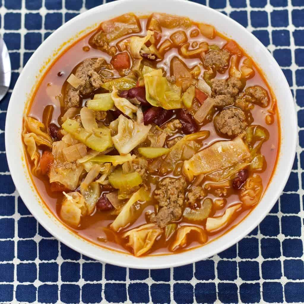 Cabbage soup in a white bowl on a blue plaid cloth