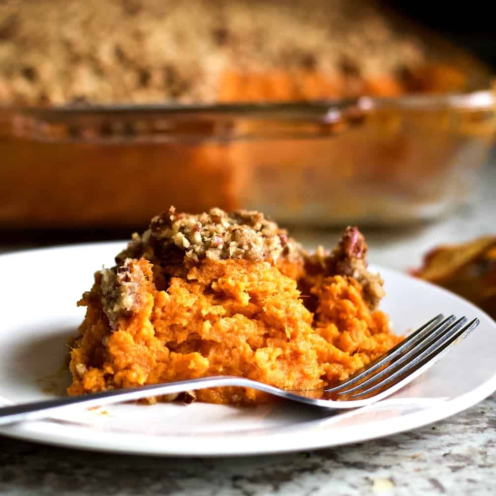 Sweet Potato Casserole serving on a white plate with the casserole dish in the background.