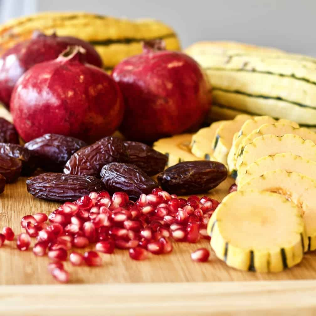 Delicata squash, pomegranate, and medjool dates on a cutting board.