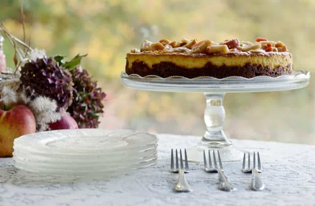 Apple Cheesecake on cake stand resting on a dessert table with fall decorations.
