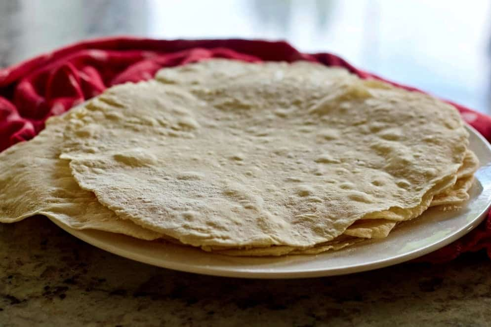 Homemade Flour Tortillas Stacked On A Plate With A Red Towel