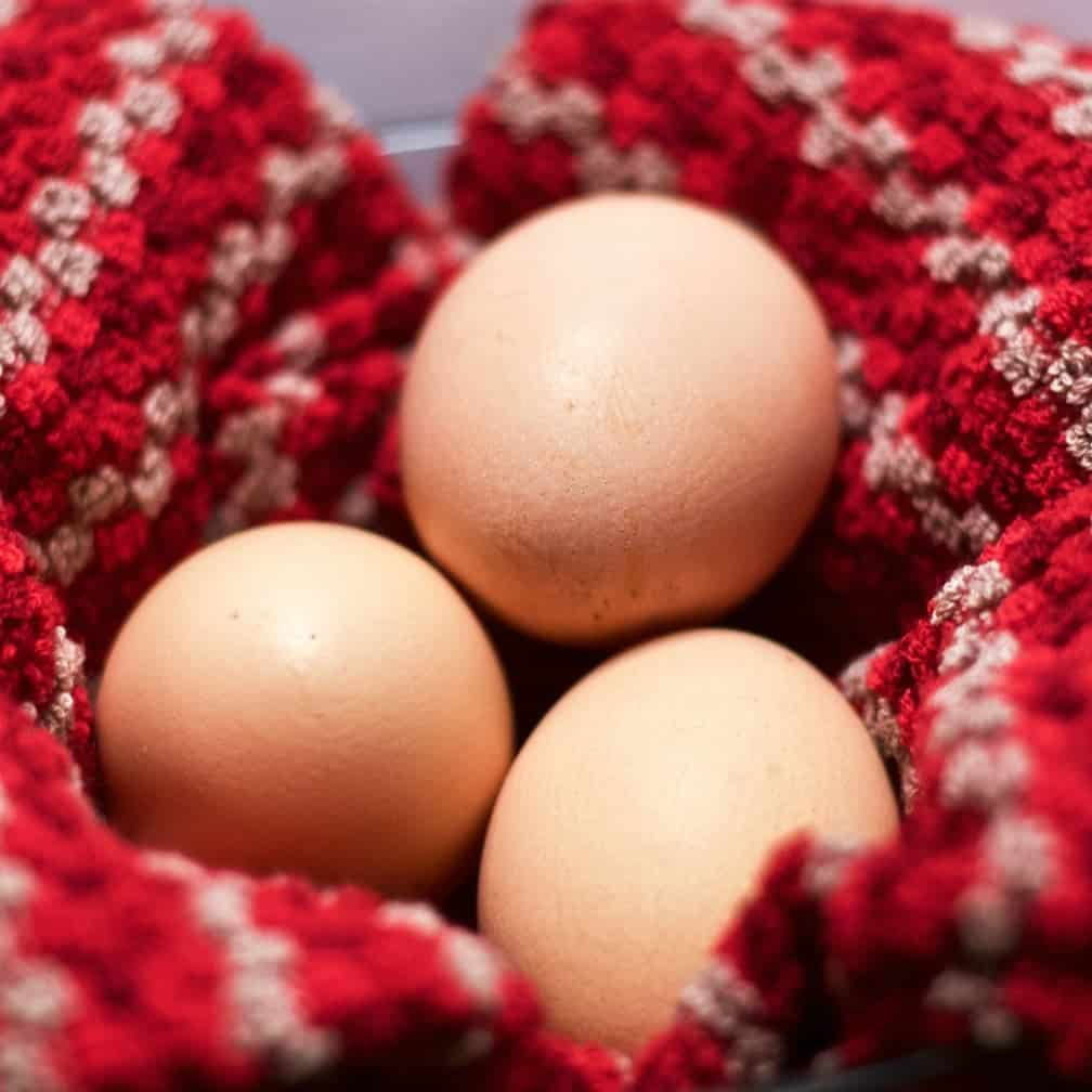 Three eggs on a red dish towel
