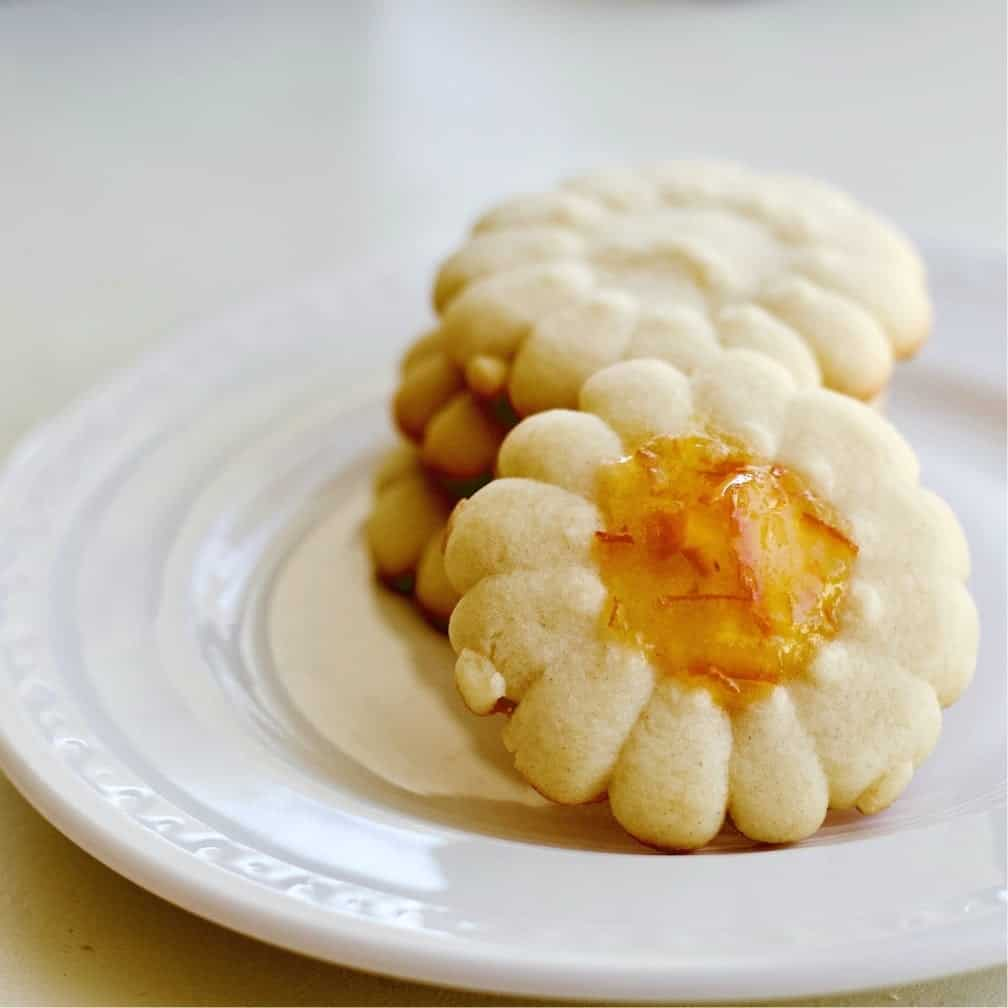 pressed Holiday cookies on a plate with marmalade in the center.