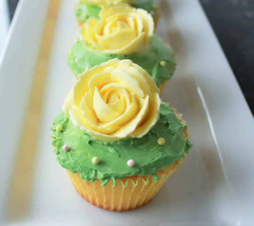 Delicious Lemon Cupcakes with a green frosting and bright yellow rose on top.