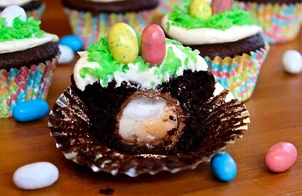 Easter egg hunt cupcakes with a cadbury egg baked into the center of the cupcake http://HomemadeFoodjunkie.com