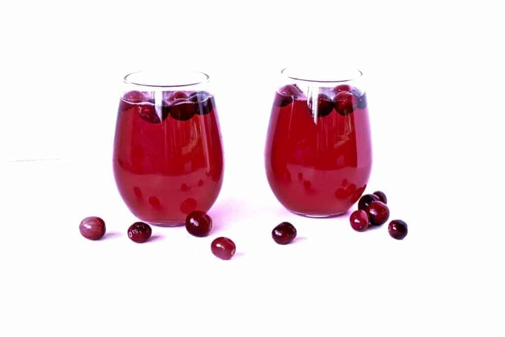 Cranberry Mimosas with fresh cranberries in two stemless glasses.