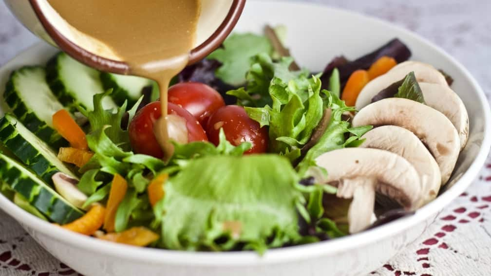 pouring creamy balsamic dressing onto a salad.