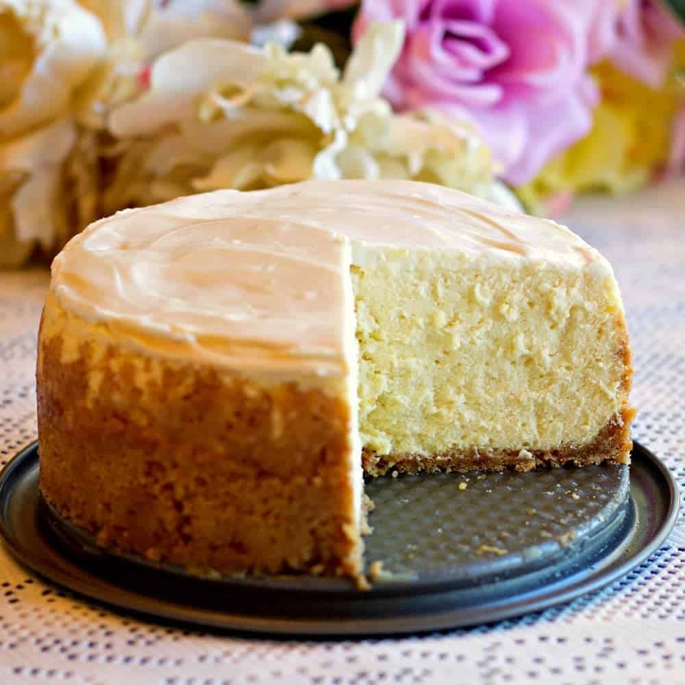 Instant Pot 6 inch New York Style Cheesecake on a spring form plate with one slice gone to expose the center of the cake.