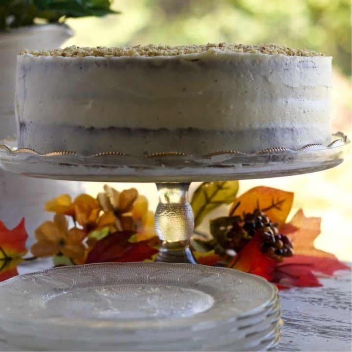 A lovely Carrot Cake with Pineapple and Pure maple Syrup on a cake stand surrounded by fall leaves