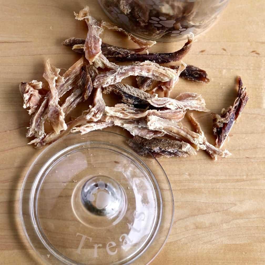 Turkey Jerky dog treats arranged around a treat jar lid.