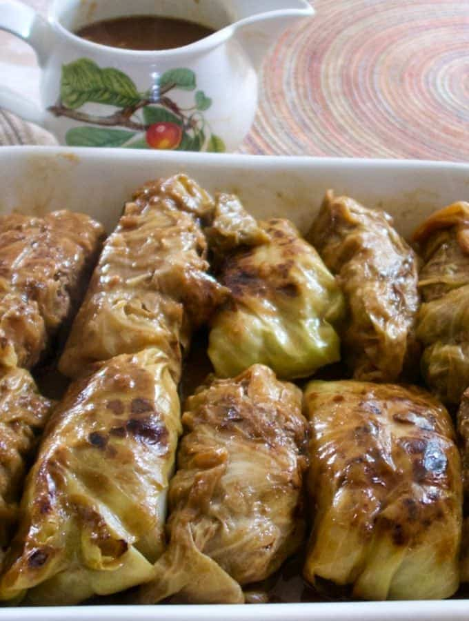 Cabbage rolls in a serving dish with gravy in a gravy server