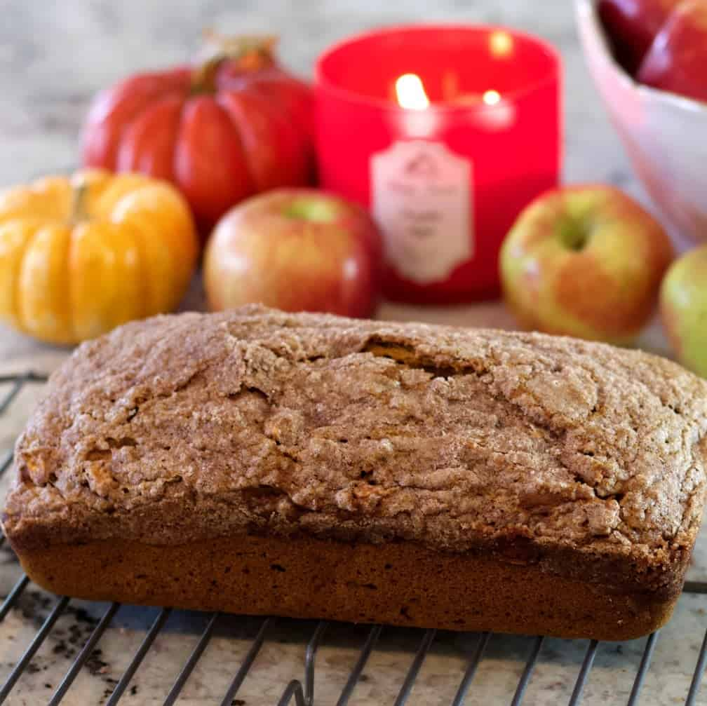 Pumpkin Apple Spice Bread on a cooling rack with Fall decor in the background.