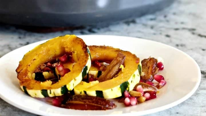 Delicata Squash Saute' on a white plate with a skillet full of this recipe in the background.