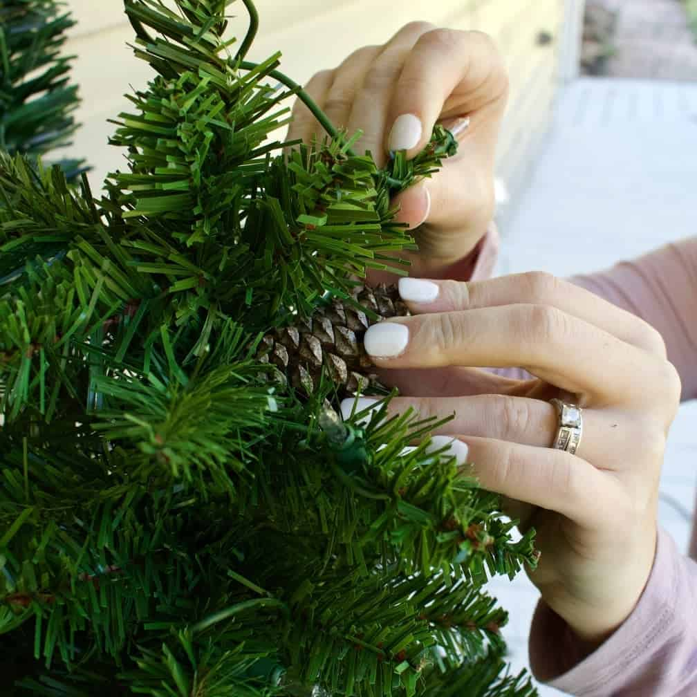 Attaching hot glued pine cones to the tree branches