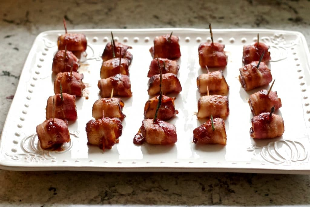 bacon wrapped water chestnuts on a white serving tray