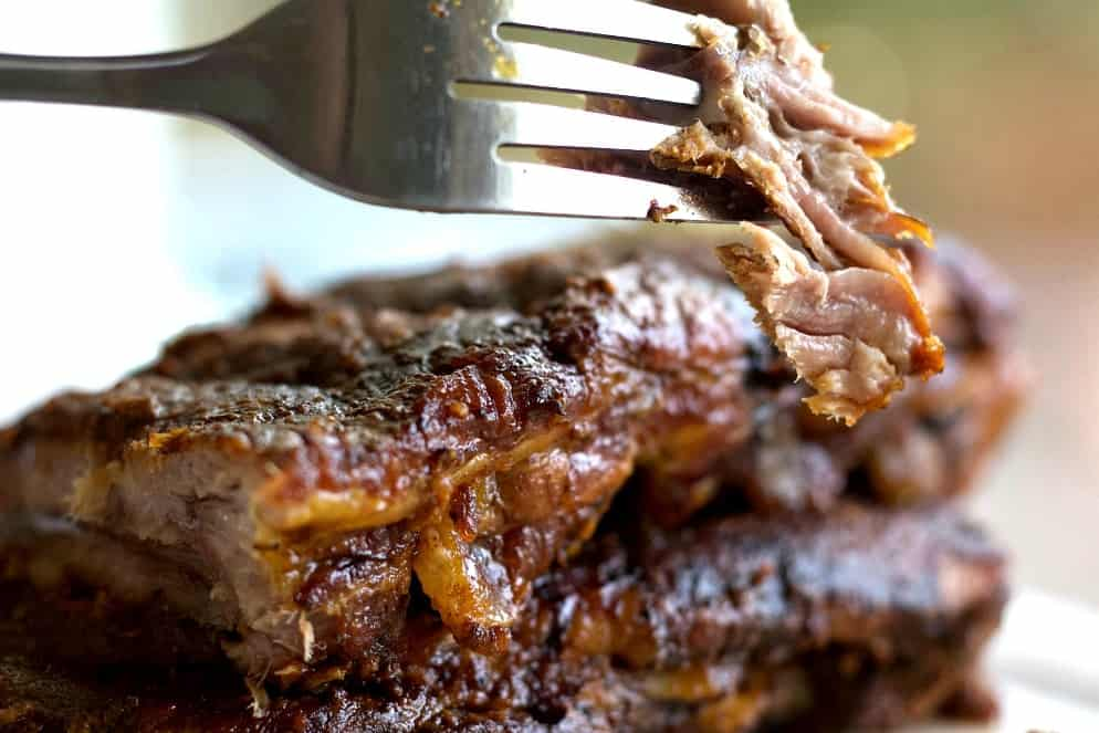 Baby Back Ribs With A Forkful Of Meat Up Close.