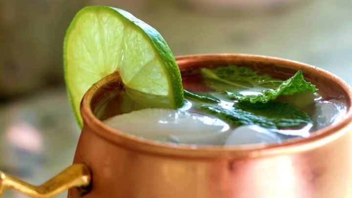Moscow mule vodka drink in a copper mug with lime and mint leaves.