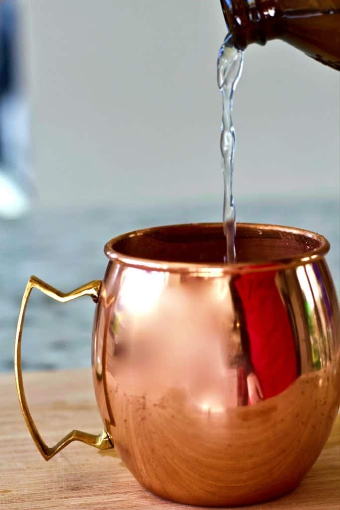 pouring vodka into a copper mug
