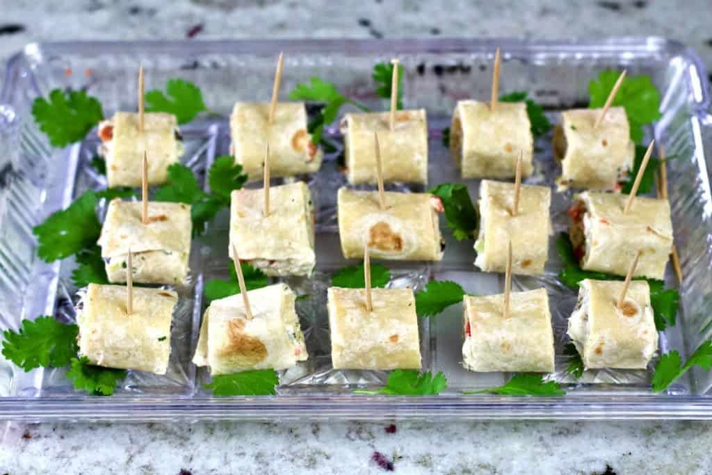 Cream cheese tortilla pinwheels on a garnished party tray.