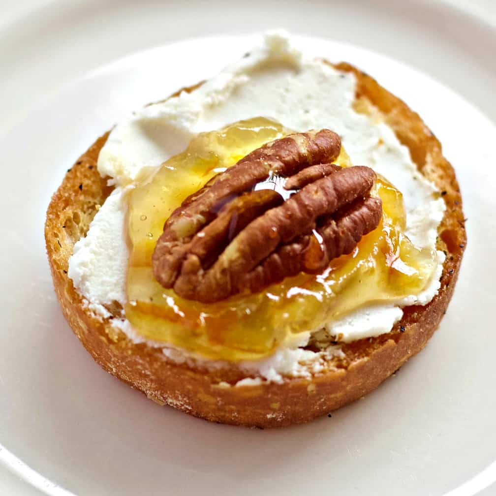 a single goat cheese crostini topped with orange marmalade and a whole pecan. Honey is drizzled on top. Sitting on a white plate.