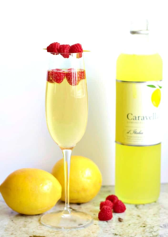 Limoncello Prosecco in a champagne flute garnished with raspberries.