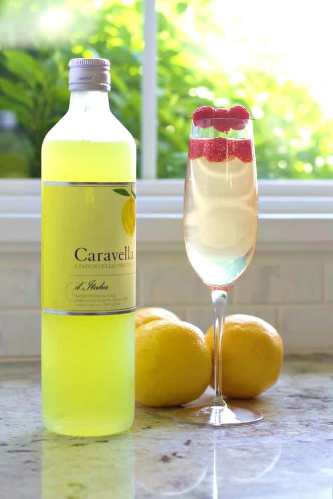 Limoncello Prosecco Cocktail with lemons and a bottle of Caravella Limoncello