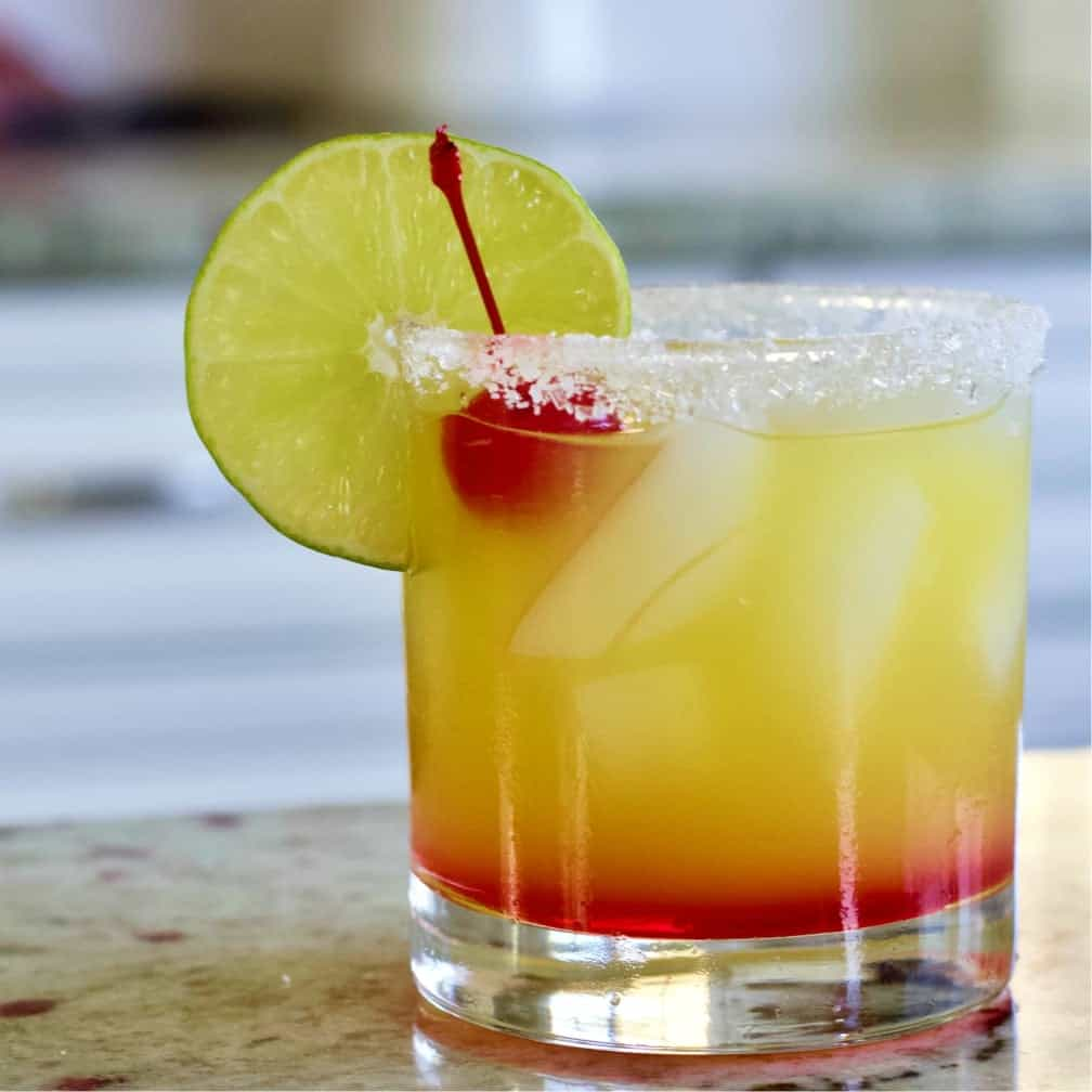 Tequila Sunrise Cocktail garnished with a lime wheel and cherry