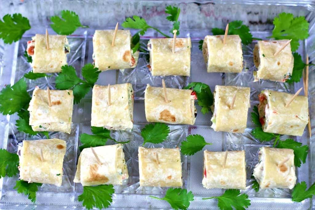 Tortilla pinwheels on a party tray with fresh cilantro