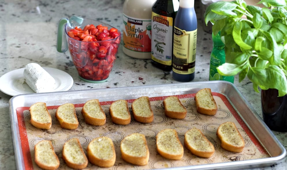 bruschetta bread slices on a baking sheet surround by the ingredients for this recipe.
