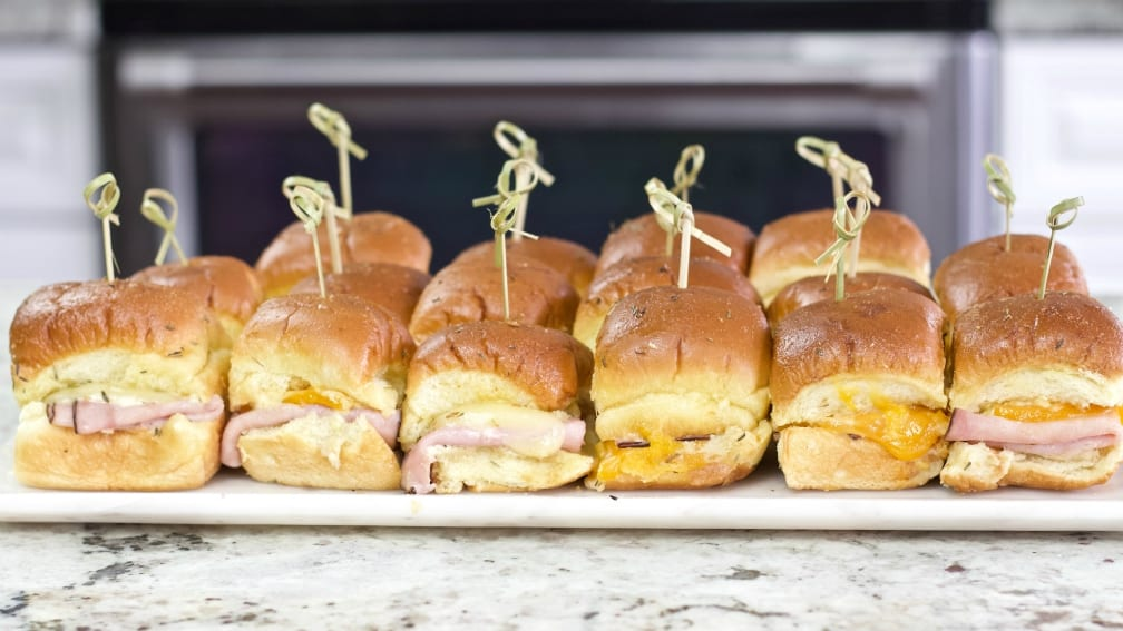 Side Shot Of Ham And Cheese Sliders With Bamboo Picks And On A Party Tray.