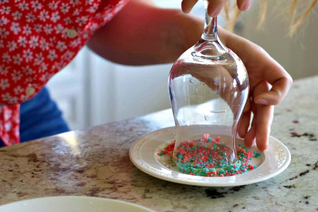 set your glass flat onto the pop rocks. Use your fingers to push the candy around the rim.