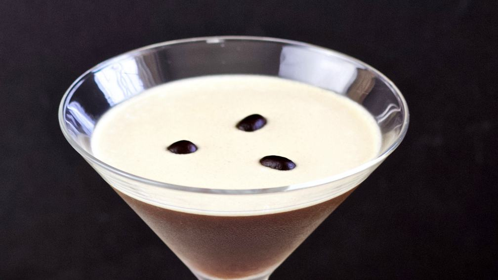 espresso martini with three coffee beans on top.