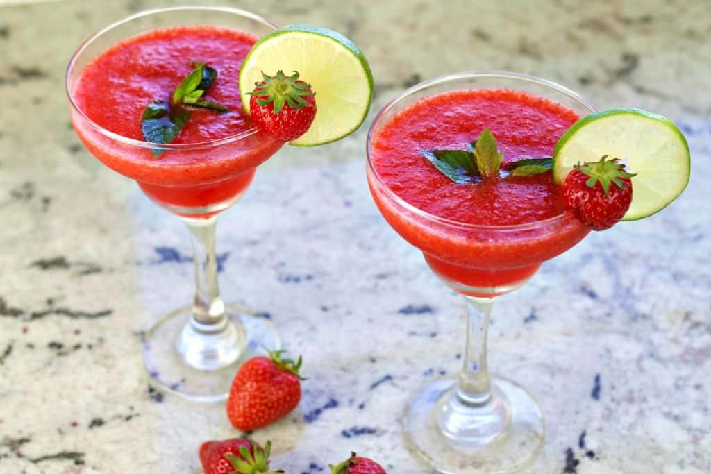 Two strawberry daiquiris garnished with mint leaves, lime wheels and a whole fresh strawberry.