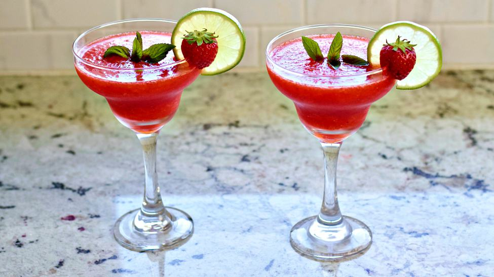 Frozen Strawberry Daiquiris sitting on a counter fully garnished.