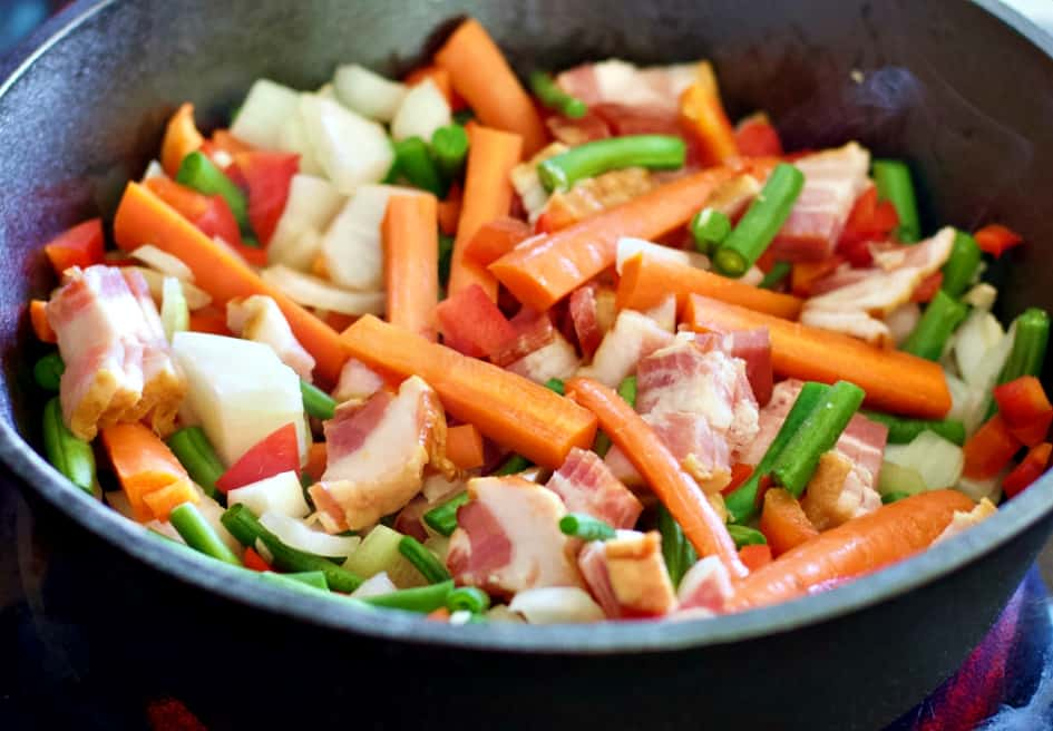 vegetables and bacon cooking in a skillet