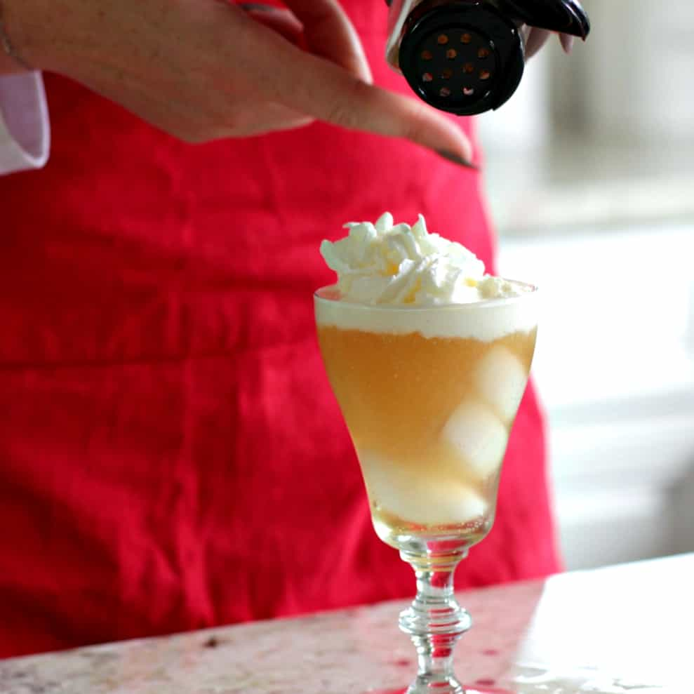 sprinkling nutmeg over the caramel vanilla cream soda cocktail