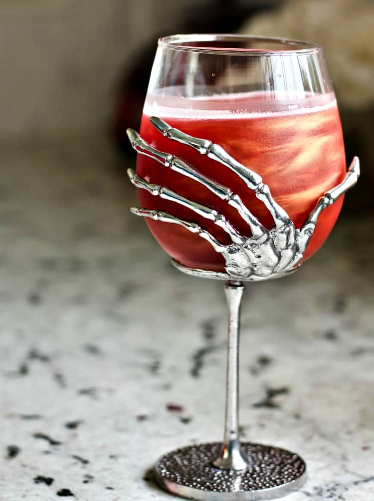 Swirling Poison Apple in a skeleton hand glass.