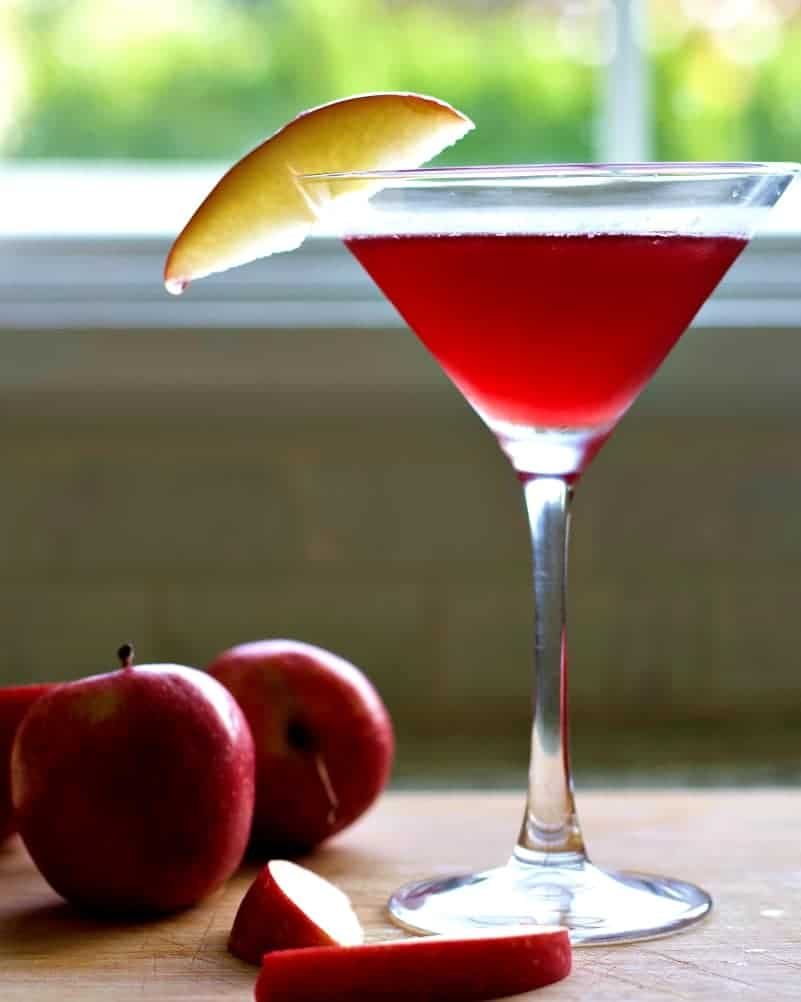 Garnished Washington Apple Drink with apples on a wooden board.