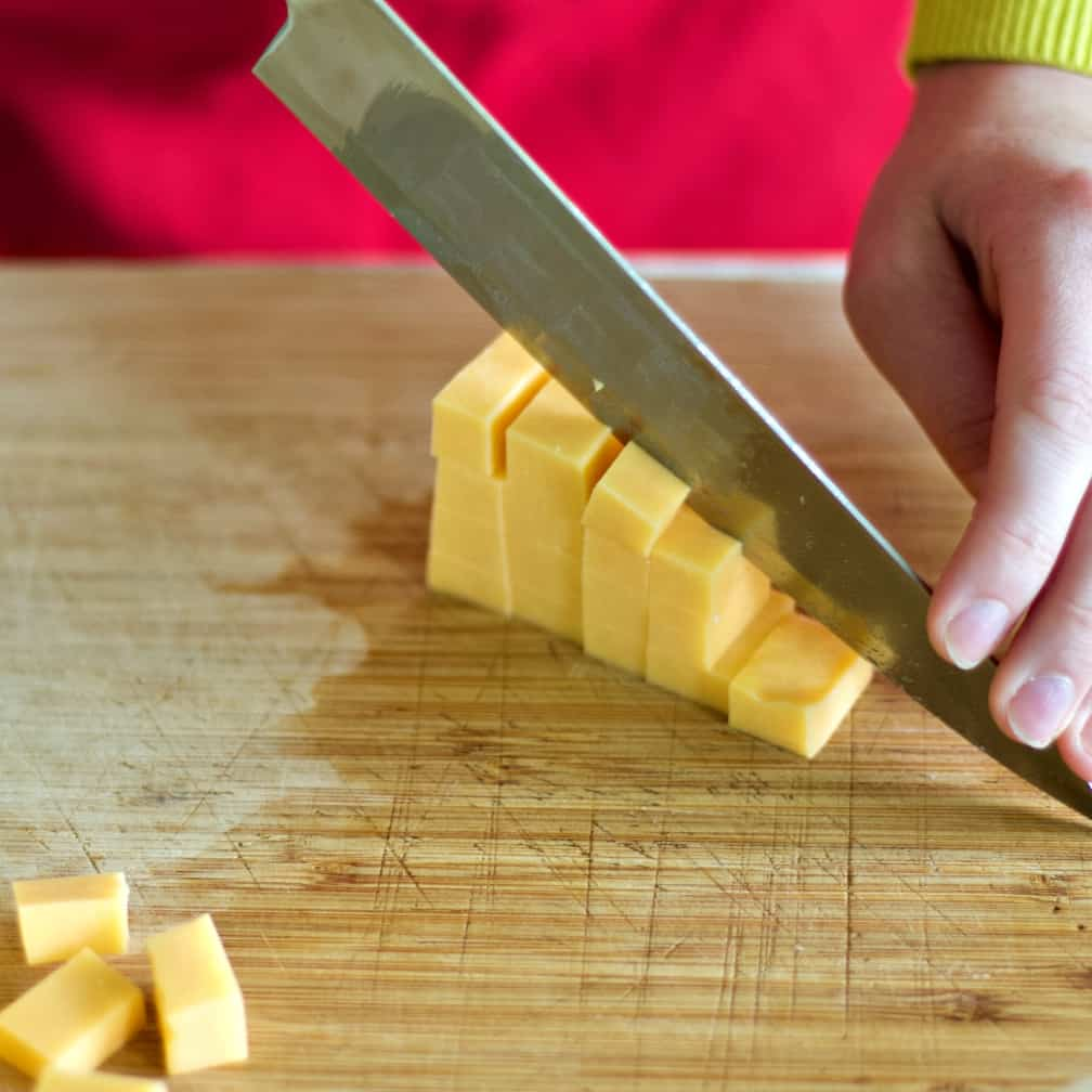 cutting cheddar cheese into cubes