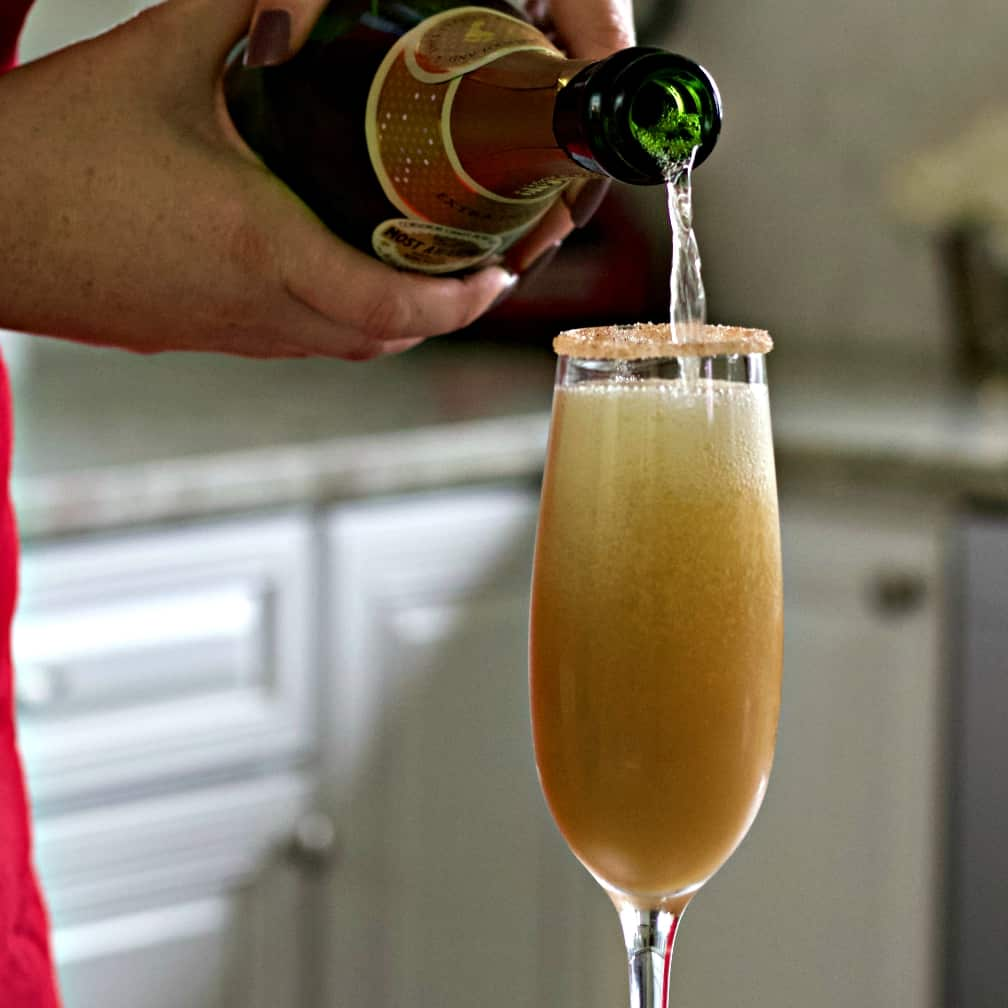 pouring sparkling white wine into pear juice