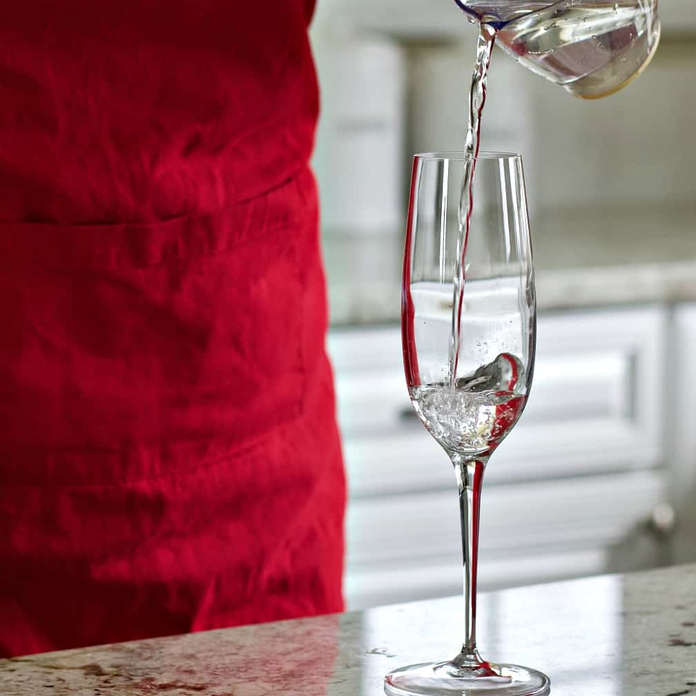Pouring white cranberry juice into a champagne flute