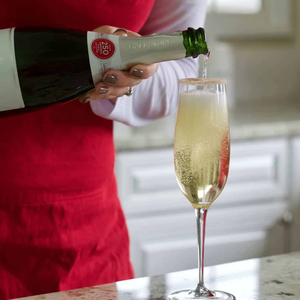 pouring sparkling wine into rimmed glass