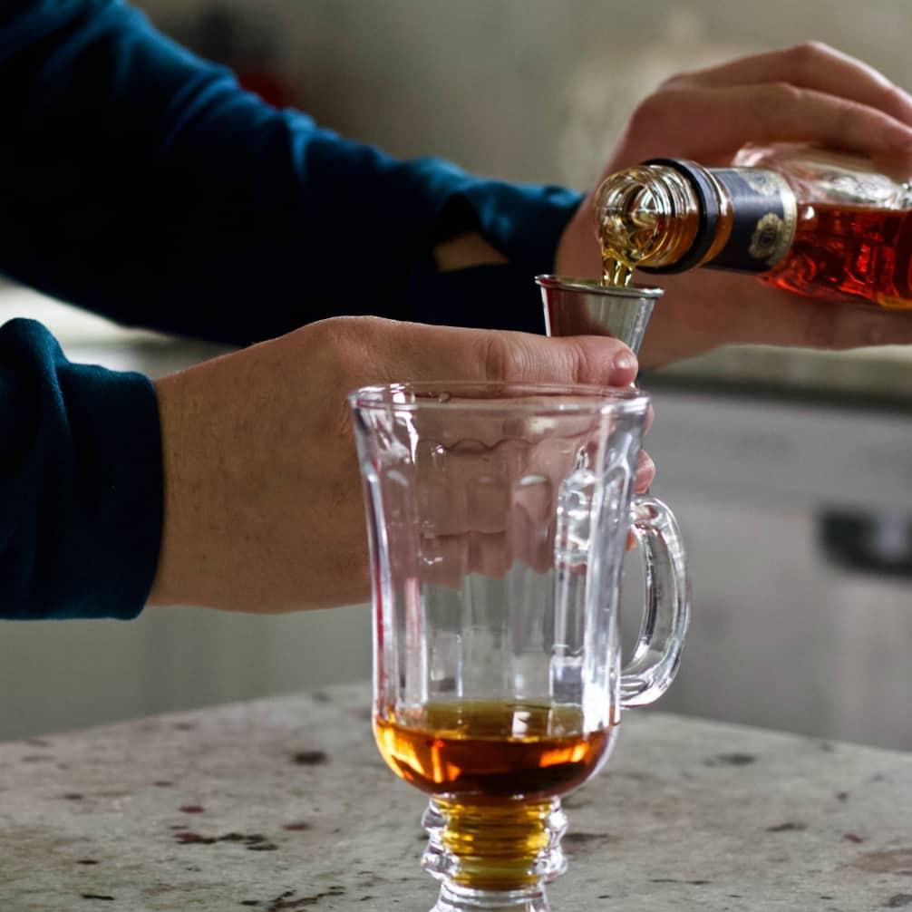 pouring brandy into a hot mug.