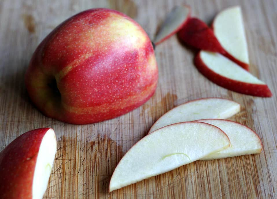 Cut apple slices with half a red apple on wooden cutting board.