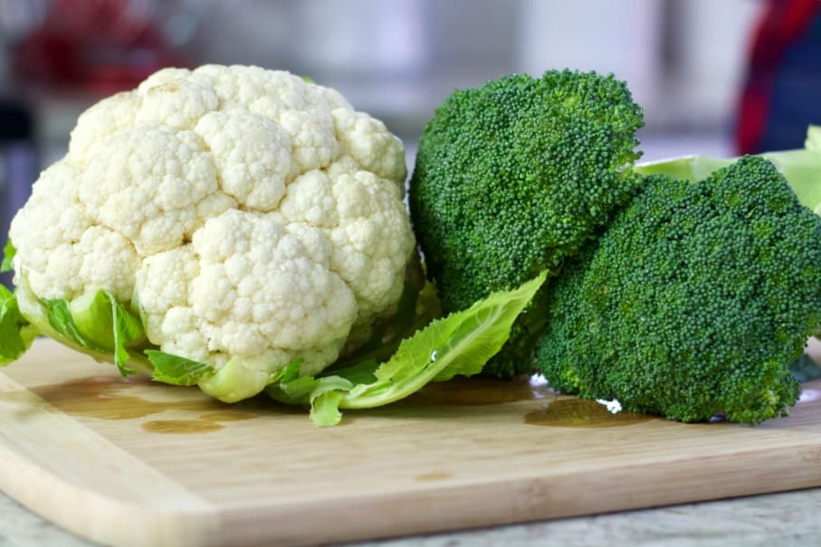 fresh cauliflower and broccoli on a cutting board.