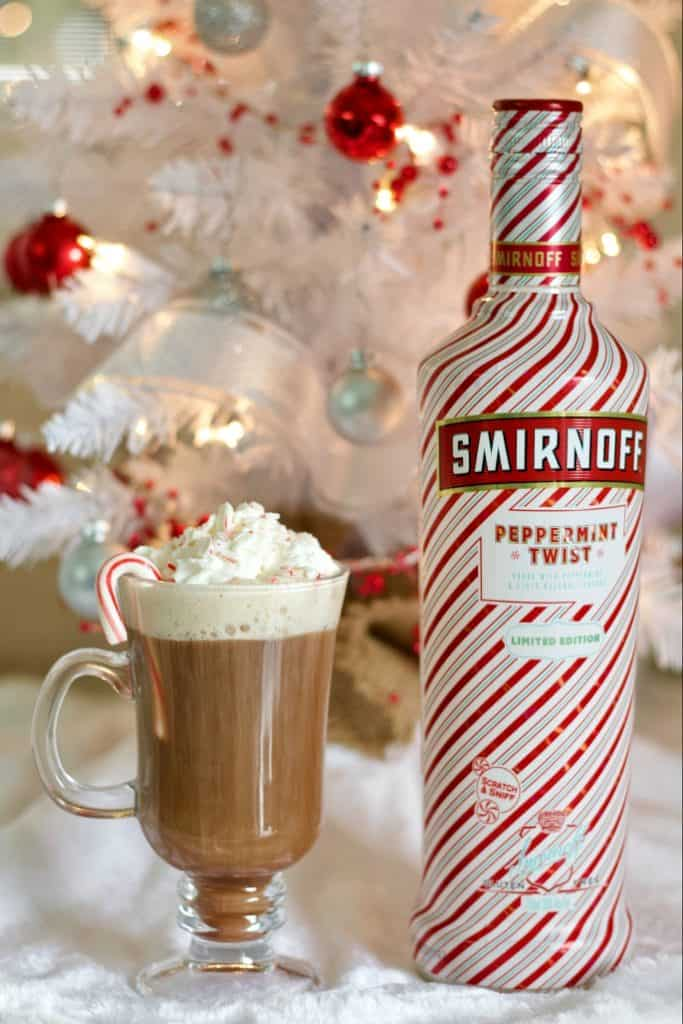 Smirnoff Peppermint Twist Vodka and peppermint hot chocolate stinger in front of a white christma tree.
